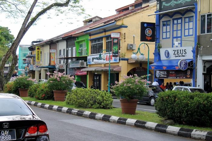 une rue et des voitures à Kuching dans l'état du Sarawak, il y a de nombreuses maisons multicolores