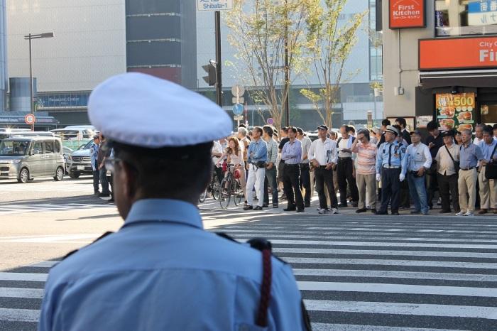 Des policiers qui empechent les gens de traverser a Osaka
