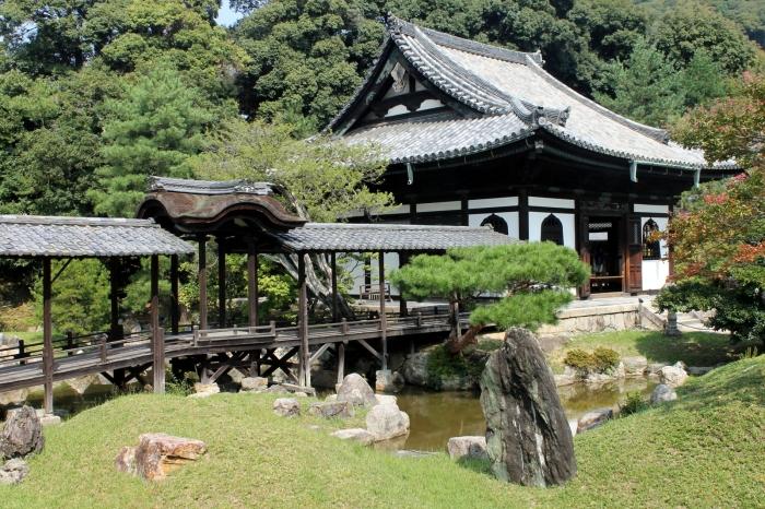 vue sur un des bâtiment du temple avec une passerelle sur la rivière