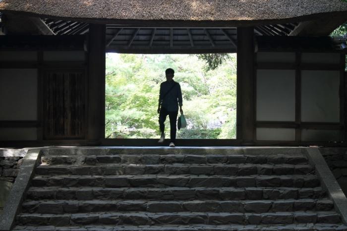 Escaliers à l'entrée du temple avec un japonais en haut des marches.