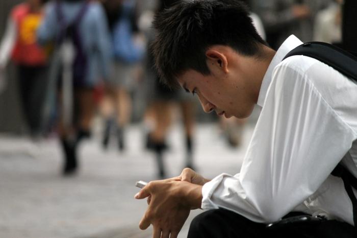 un japonais qui envoie un texto dans la rue