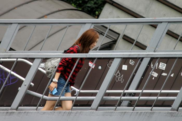 Une japonaise qui monte sur une passerelle dans la ville de Tokyo et plus précisément dans le quartier d'Harajuku.
