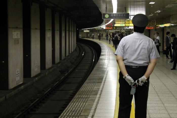 Il regarde le métro qui arrive avec les bras croisés